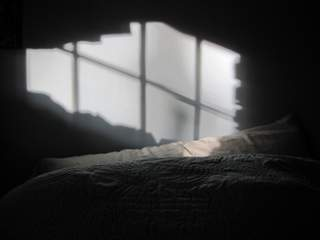 Bed with shadows on wall